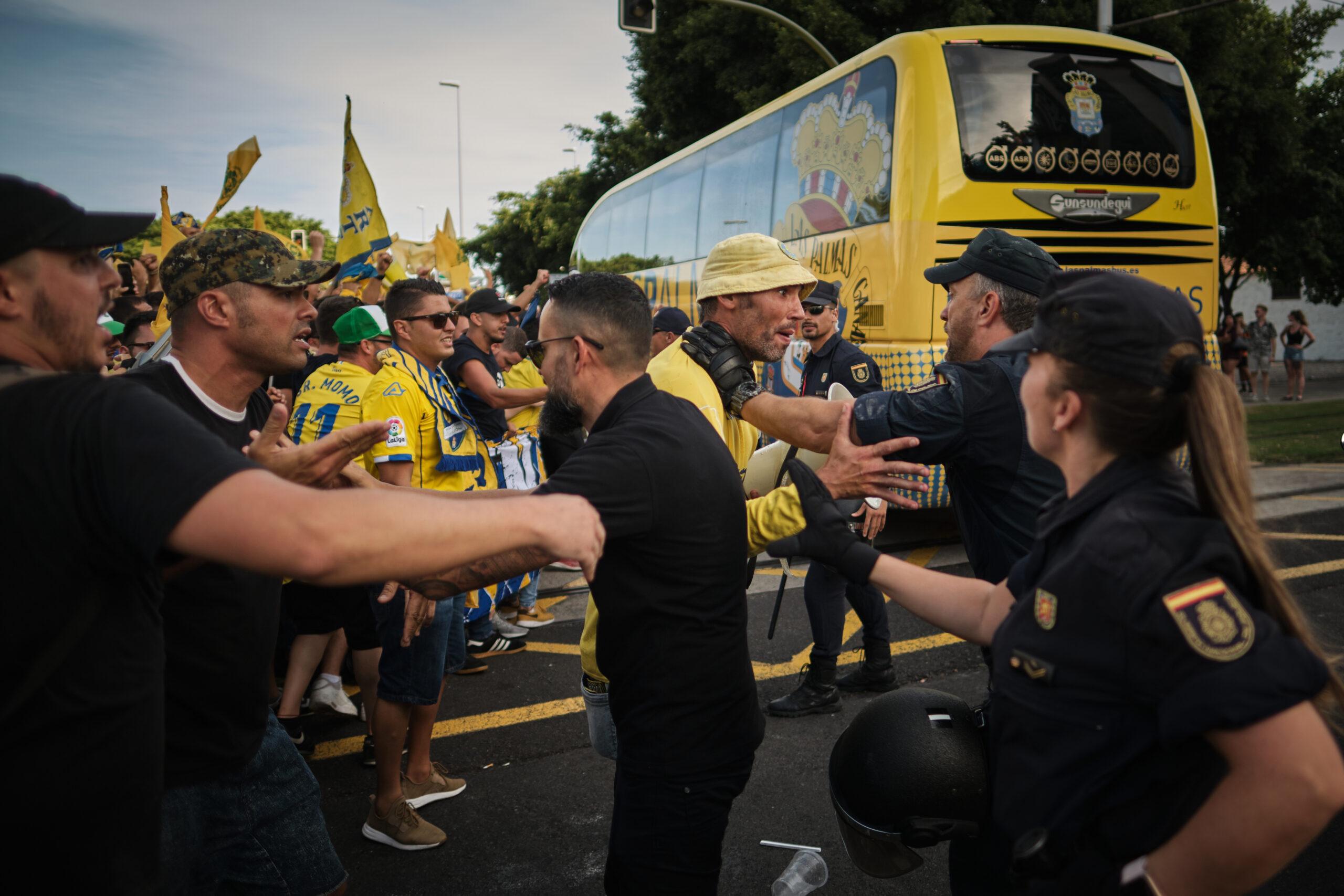 Primer Premio. Categoría: Deportes (Serie). Efectivos de la Policia Nacional, tratan de calmar a los ultras de la UD Las Palmas ante el paso del autobús de su equipo. Julio 9, 2019. Santa Cruz de Tenerife. Andrés Gutiérrez
