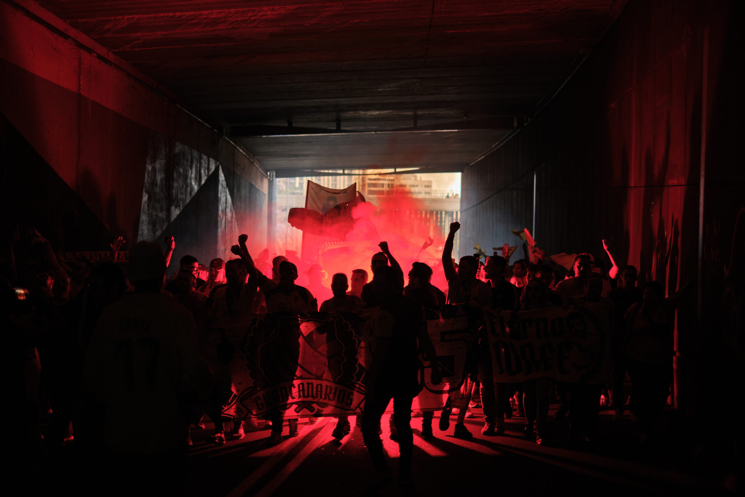 Primer Premio. Categoría: Deportes (Serie). Aficionados y ultras de la UD Las Palmas, encienden bengalas y cantan durante el recorrido desde el muelle de la ciudad hasta el estadio. El grupo debe ser escoltado por efectivos de la Policía para evitar enfrentamiento entra las dos hinchadas. Julio 9, 2019. Santa Cruz de Tenerife. Andrés Gutiérrez