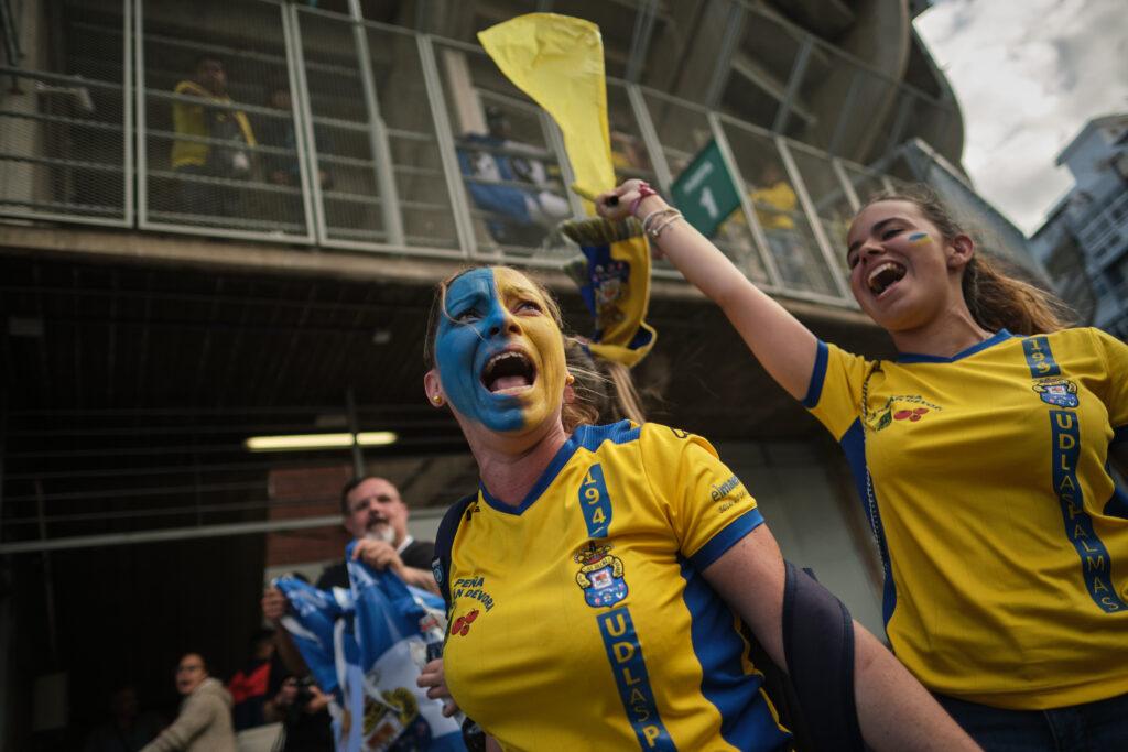 Primer Premio. Categoría: Deportes (Serie). Dos aficionadas de la UD Las Palmas entran al estadio entre cánticos y gritos. Julio 9, 2019. Santa Cruz de Tenerife. Andrés Gutiérrez