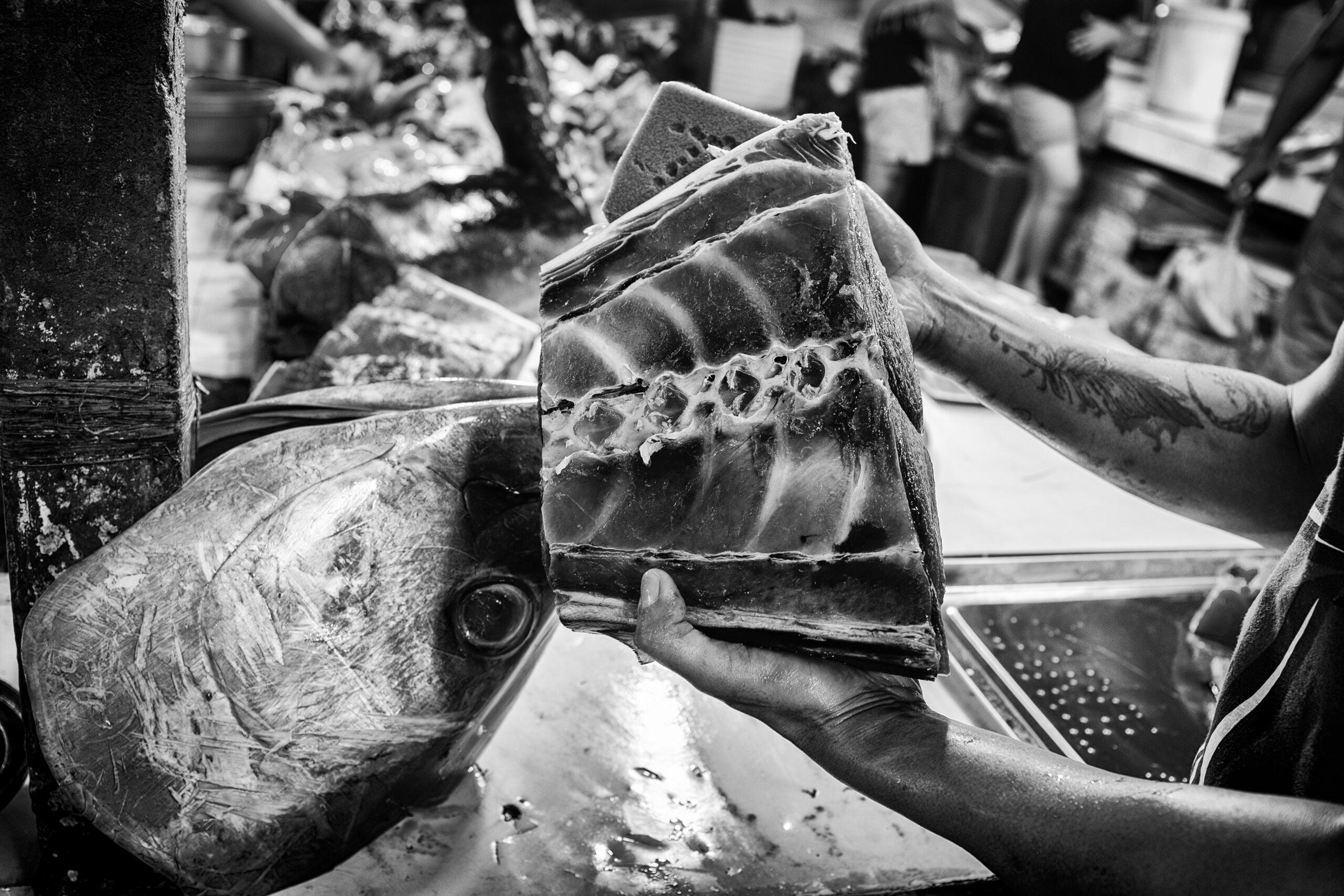 Primer Premio. Categoría: Mejor trabajo en el exterior (Serie). En el mercado de la ciudad filipina de General Santos un vendedor muestra un pedazo de lomo de yellowfin. Durante la primera semana de septiembre se celebra en esta localidad el festival del atún, una especie de carnaval pero con el atún como temática principal. Nando Rivero