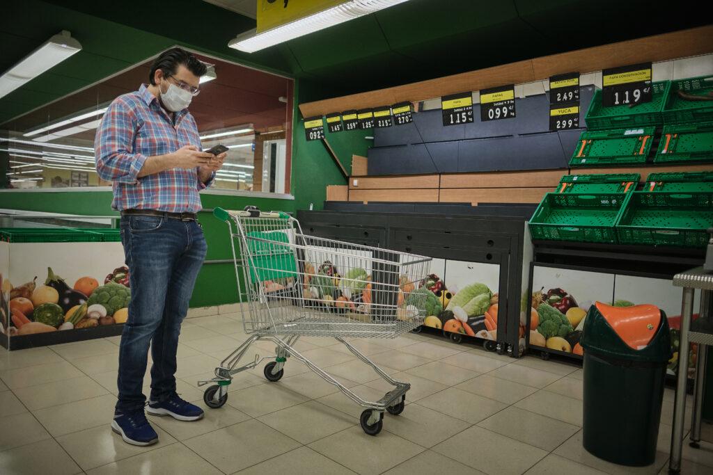 Segundo Premio. Categoría: Sociedad (Serie). Un hombre observa su móvil en un supermercado totalmente vacío como consecuencia de las compras compulsivas, generadas por el nerviosismo de la población, durante los primeros días del estado de alarma. Marzo 13, 2020. Santa Cruz de Tenerife. Andrés Gutiérrez