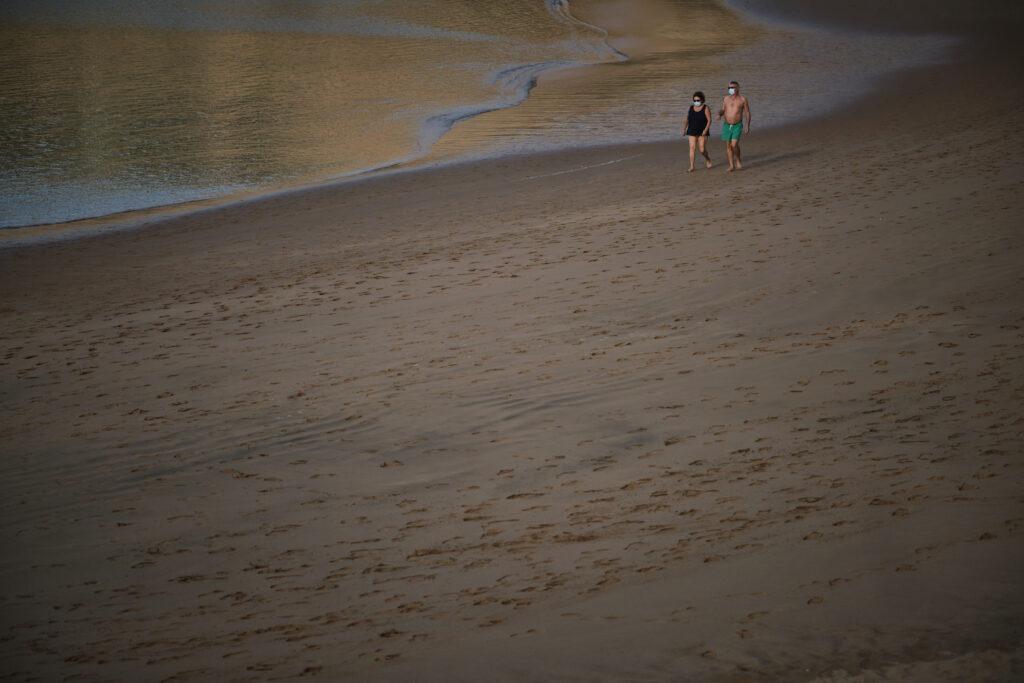 Segundo Premio. Categoría: Sociedad (Serie). Dos personas con mascarilla caminan por la una vacía playa de Las Teresitas. Diciembre 18, 2020. Santa Cruz de Tenerife.  La falta de turistas en las Islas deja imágenes de playas completamente desoladas. Andrés Gutiérrez