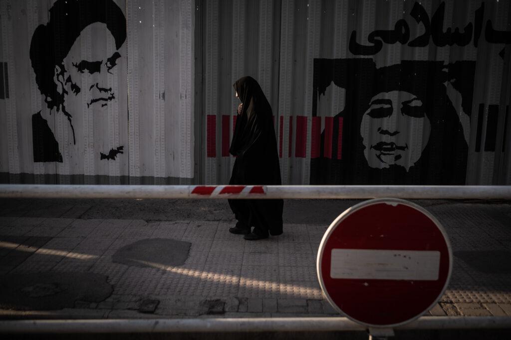 Segundo Premio. Categoría: Mejor trabajo en el exterior (Serie). Un mujer camina vistiendo un chador por una céntrica calle de la ciudad de Qom. En el fondo se puede ver una imagen del Ayatollah Jomeini, líder espiritual y politico de la revolución Iraní a finales de la década de los setenta. Octubre 10, 2019. Qom, Irán.   Reza Shah prohibió el uso del chador en 1936 dentro su política de occidentalización del país. Esa prohibición se relajó bajo el reinado de El Shah Mohammad Reza Pahlaví. En la actualidad la revolución iraní ve el chador conforme al código de vestimenta islámico. El chador es un instrumento de salvaguarda de la identidad nacional y religiosa frente a la occidentalización. La república islámica de Irán promociona el uso de esta prenda y en ciertos ámbitos la impone.  El chador es un símbolo de la revolución iraní que choca frontalmente con el pensamiento de los más jóvenes del país. La presencia de las mujeres en todas las esferas sociales y su alto nivel de preparación, facilita la reivindicación de sus derechos todavía postergados por la tradición islámica.  Andrés Gutiérrez