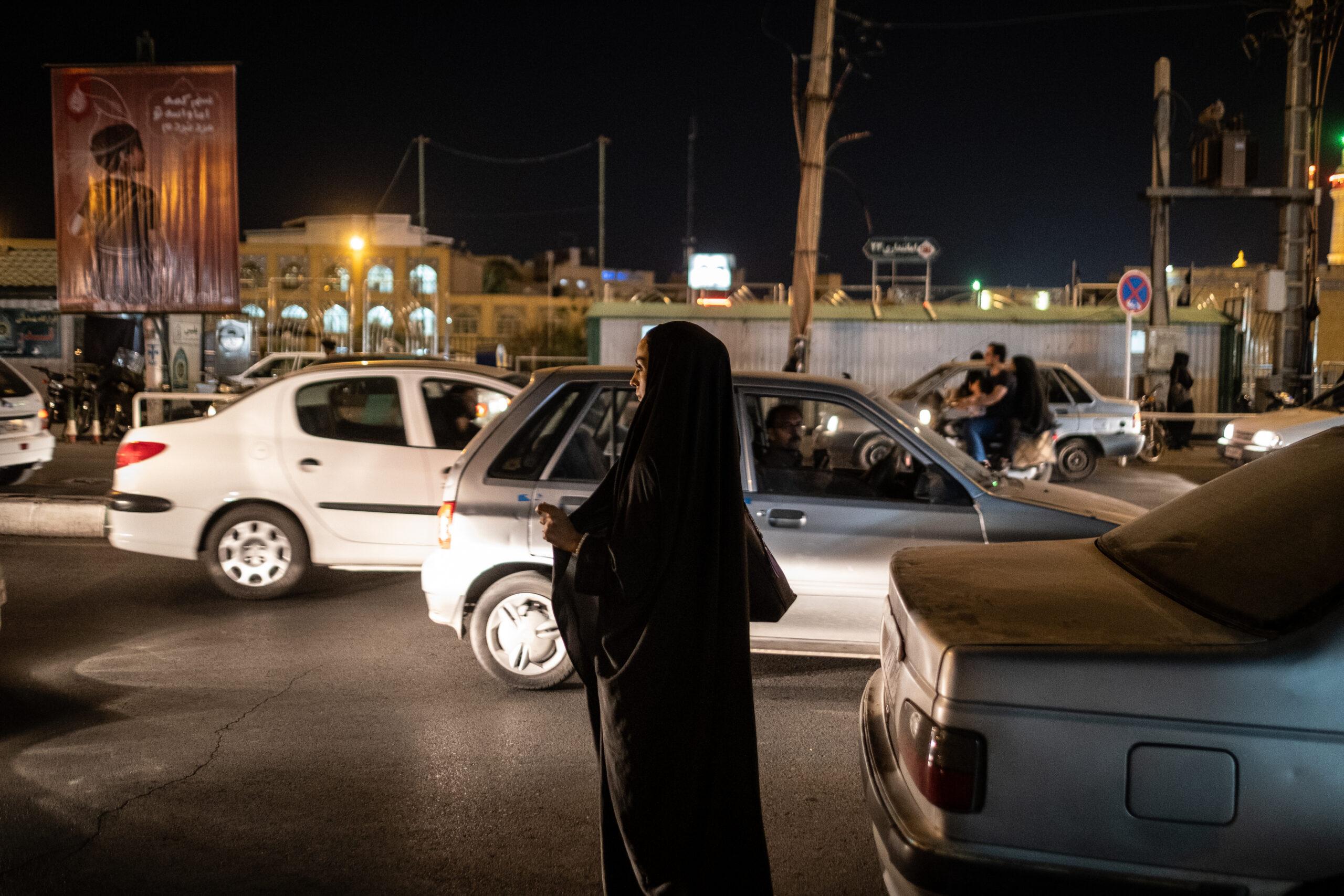 Segundo Premio. Categoría: Mejor trabajo en el exterior (Serie). Un mujer vistiendo un chador espera a un taxi en la calle principal de la ciudad de Qom. El hecho de ver a una mujer sola durante la noche hace que los conductores le increpen desde las ventanas de sus coches. Octubre 9, 2019. Qom, Irán.   Reza Shah prohibió el uso del chador en 1936 dentro su política de occidentalización del país. Esa prohibición se relajó bajo el reinado de El Shah Mohammad Reza Pahlaví. En la actualidad la revolución iraní ve el chador conforme al código de vestimenta islámico. El chador es un instrumento de salvaguarda de la identidad nacional y religiosa frente a la occidentalización. La república islámica de Irán promociona el uso de esta prenda y en ciertos ámbitos la impone.  El chador es un símbolo de la revolución iraní que choca frontalmente con el pensamiento de los más jóvenes del país. La presencia de las mujeres en todas las esferas sociales y su alto nivel de preparación, facilita la reivindicación de sus derechos todavía postergados por la tradición islámica. Andrés Gutiérrez