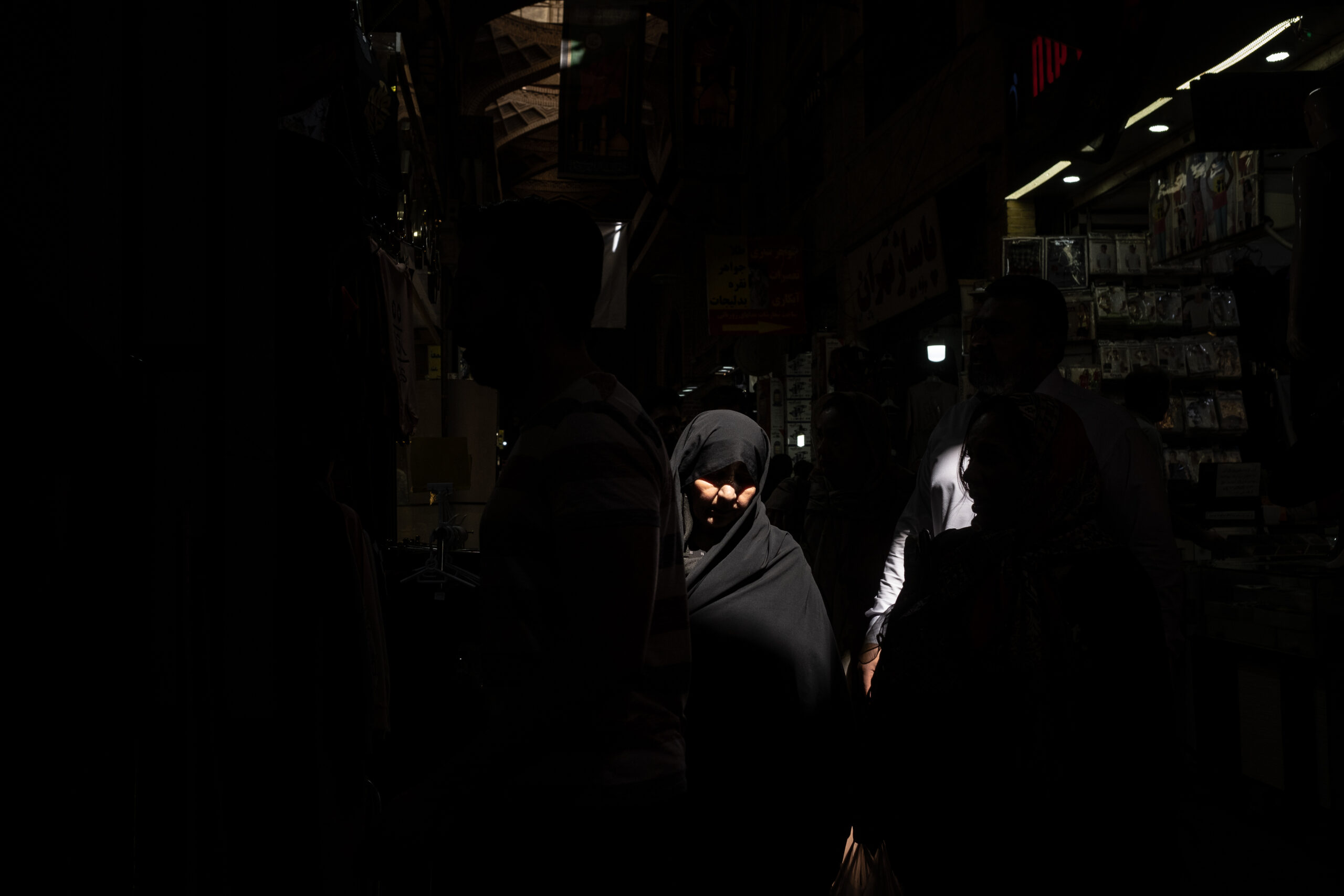 Segundo Premio. Categoría: Mejor trabajo en el exterior (Serie). Una mujer camina vistiendo su chador color negro por el Gran Bazar en la ciudad de Teherán. Septiembre 30, 2019. Irán.   Reza Shah prohibió el uso del chador en 1936 dentro su política de occidentalización del país. Esa prohibición se relajó bajo el reinado de El Shah Mohammad Reza Pahlaví. En la actualidad la revolución iraní ve el chador conforme al código de vestimenta islámico. El chador es un instrumento de salvaguarda de la identidad nacional y religiosa frente a la occidentalización. La república islámica de Irán promociona el uso de esta prenda y en ciertos ámbitos la impone.  El chador es un símbolo de la revolución iraní que choca frontalmente con el pensamiento de los más jóvenes del país. La presencia de las mujeres en todas las esferas sociales y su alto nivel de preparación, facilita la reivindicación de sus derechos todavía postergados por la tradición islámica. Andrés Gutiérrez