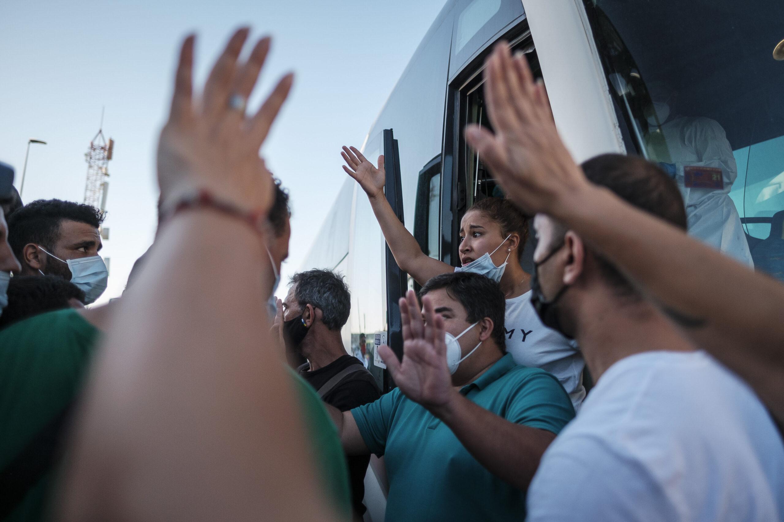 Mención de Honor . Categoría: Sociedad (Serie). ARGUINEGUÍN (GRAN CANARIA) (ESPAÑA), 17/11/2020.- Entre 200 y 250 inmigrantes marroquíes que se encontraban en el muelle de Arguineguín han sido conducidos por la Policía fuera del campamento de la Cruz Roja y serán trasladados en autobuses dispuestos por el Ayuntamiento de Mogán a Las Palmas de Gran Canaria. El grupo está recibiendo la ayuda improvisada como intérprete de Sarah Bettache (detrás), una ciudadana marroquí que llegó el lunes a Arguineguín desde Francia tras enterarse de que su hermano podía haber llegado en patera a la isla y ha conseguido encontrarlo en el muelle. Ángel Medina G.